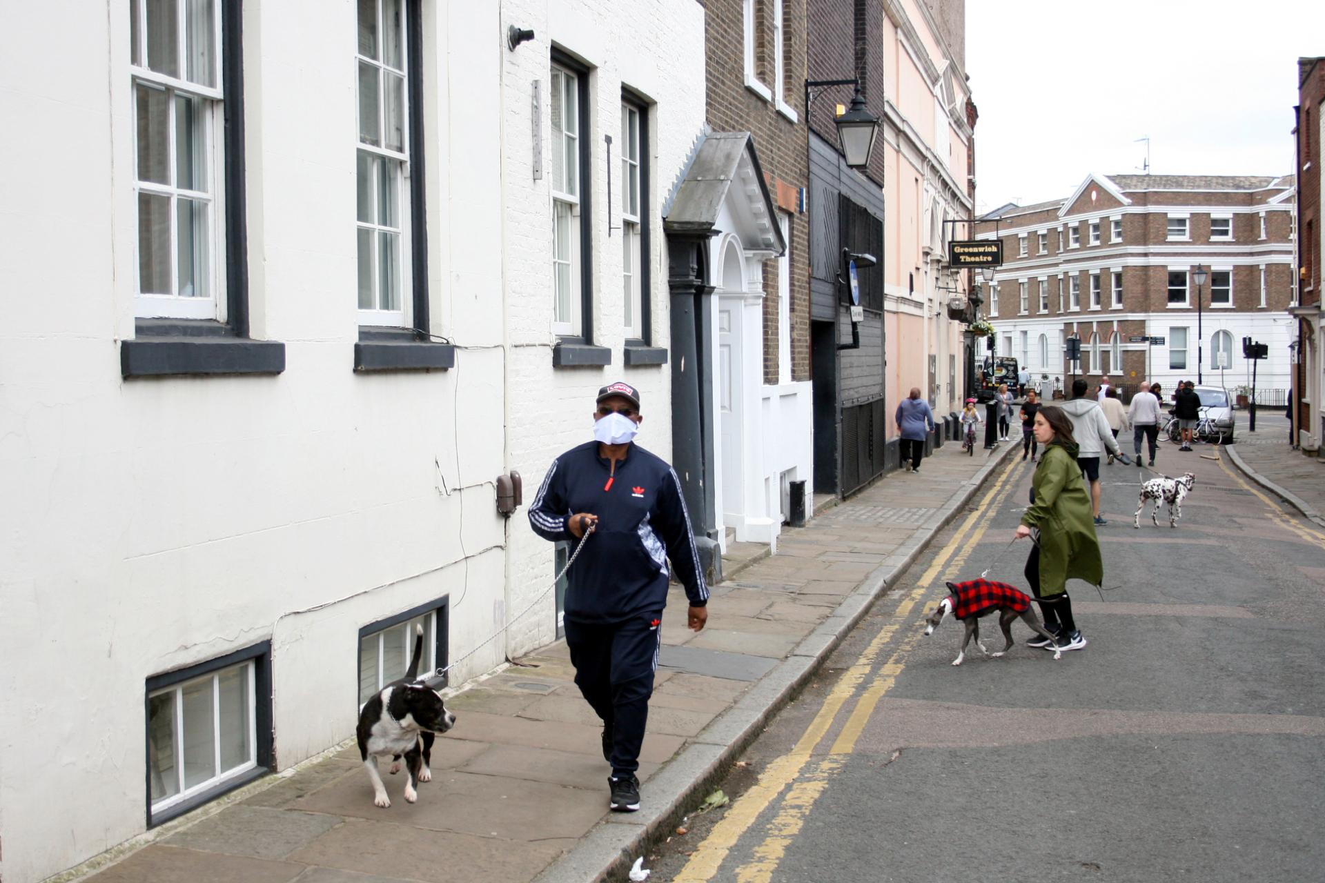 Homem com máscara caminha com seu cachorro em Greenwich, Londres