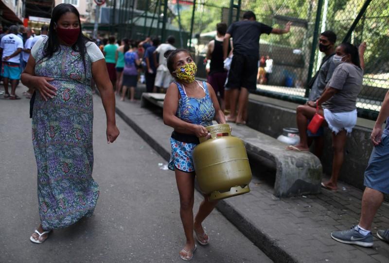 mulher carrega botijão de gás