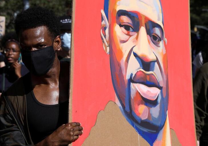 Manifestante segura cartaz com rosto de George Floyd durante protesto em NY