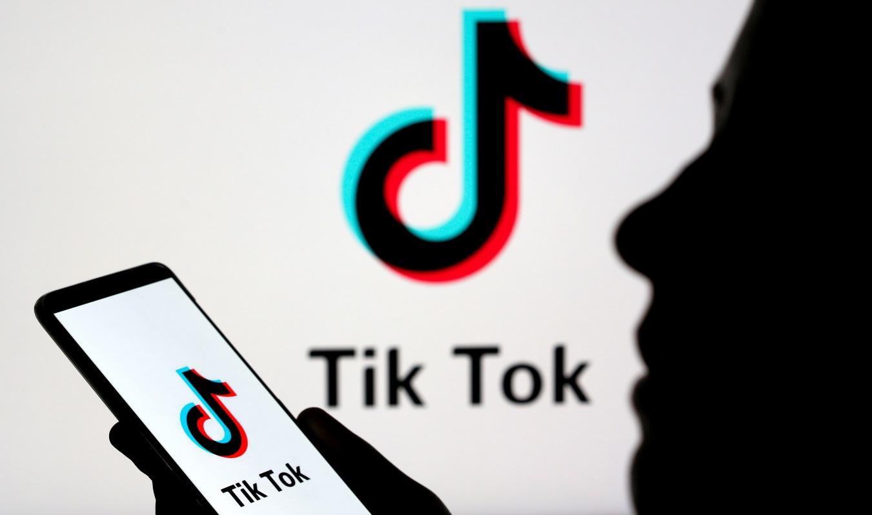 Pessoa manipula smartphone com logotipo da TikTok