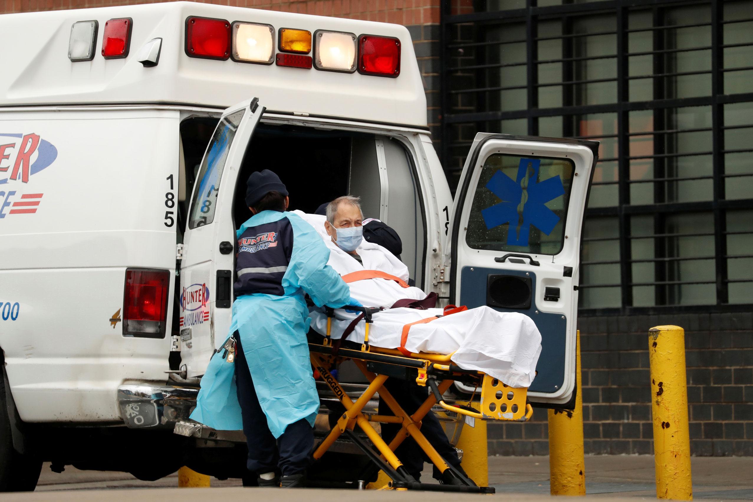 Paciente com Covid-19 é transportado para dentro de ambulância em Nova York