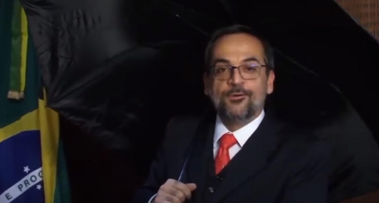 Ex-ministro da Educação Abraham Weintraub usa guarda-chuva