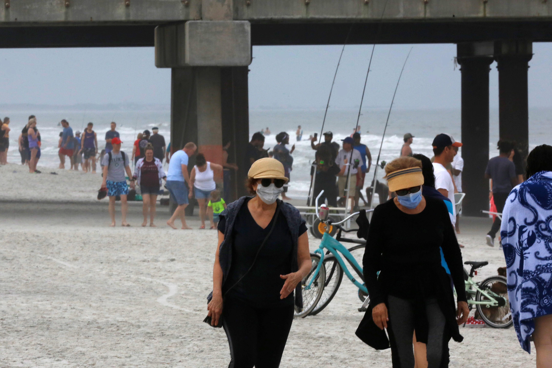 Pessoas caminham em praia na cidade de Jacksonville, na Flórida