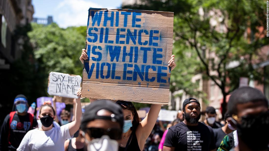 """Manifestante segura cartaz que diz """"O silêncio branco é uma violência branca""""."""