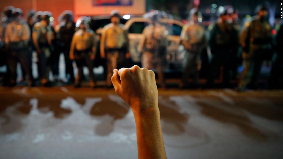 Um manifestante levanta o punho durante uma manifestação.