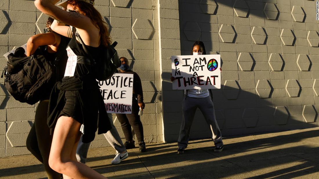 """Mulher negra segura cartaz de protesto que diz """"Eu não sou uma ameaça""""."""