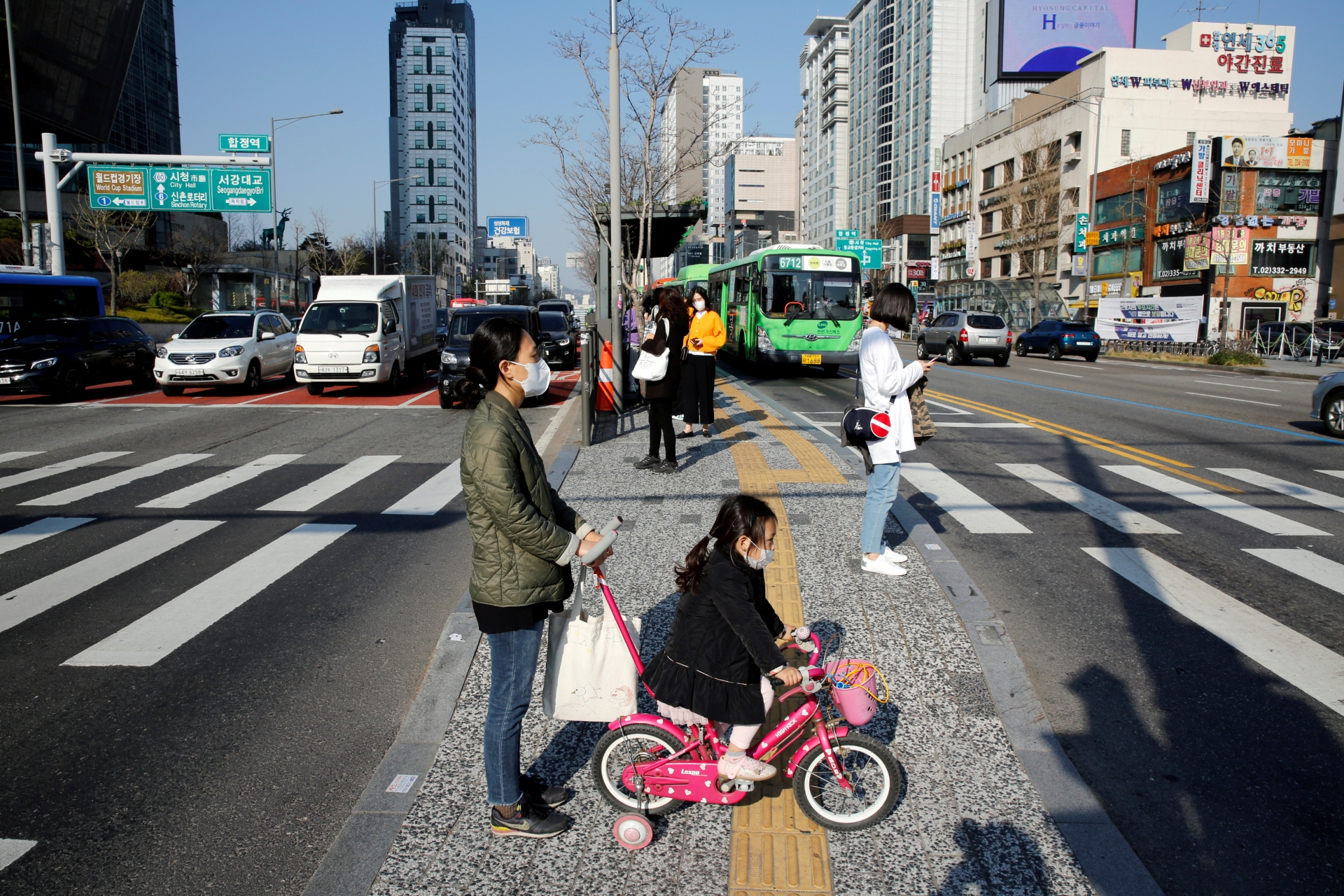 Mãe e filha usam máscaras enquanto caminham por avenida no centro de Seul