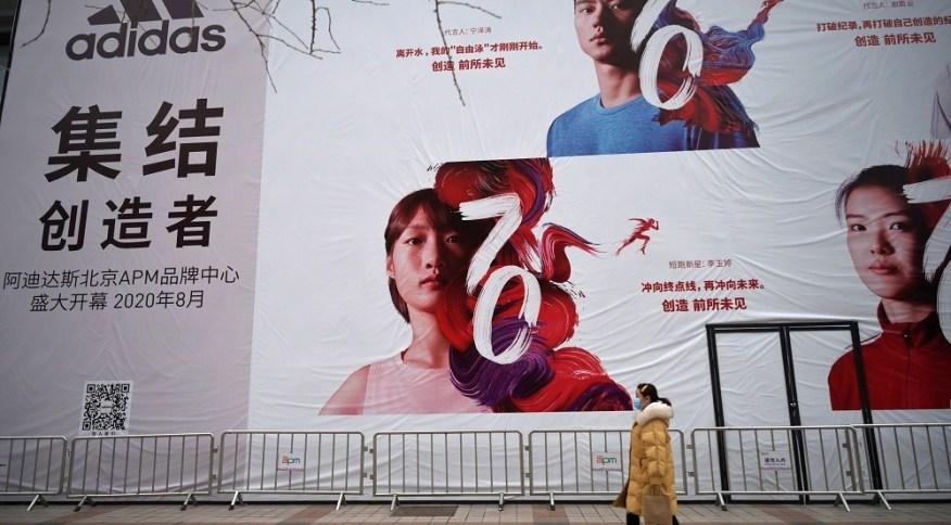 Mulher com máscara de proteção contra coronavírus passa por banner da Adidas em Pequim, China 20/02/2020