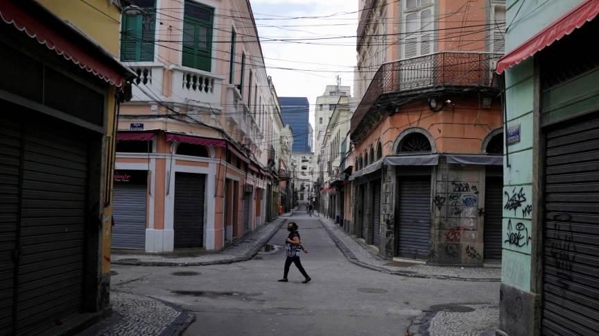 Mulher usando máscara anda ao lado das lojas fechadas no centro do Rio de Janeiro durante pandemia do coronavírus