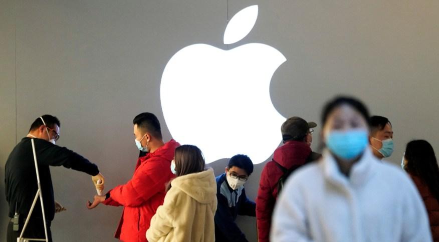 Clientes usam máscaras de proteção enquanto aguardam para medir temperatura em loja da Apple, em meio a surto do novo coronavírus