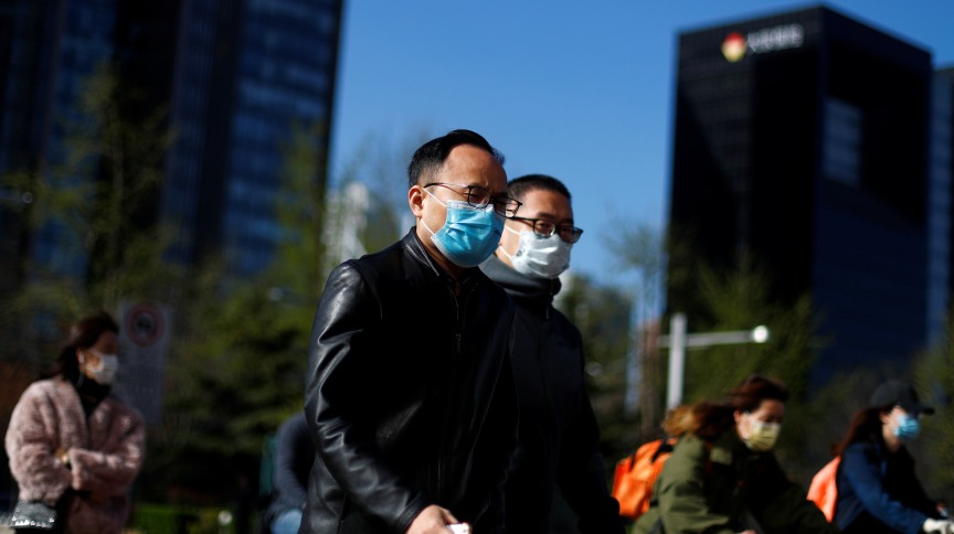 People wear masks as they head to work during morning rush hour, amid the outbreak of  coronavirus disease (COVID-19), in the central business district in Beijing, China, April 2, 2020. REUTERS/Thomas Peter