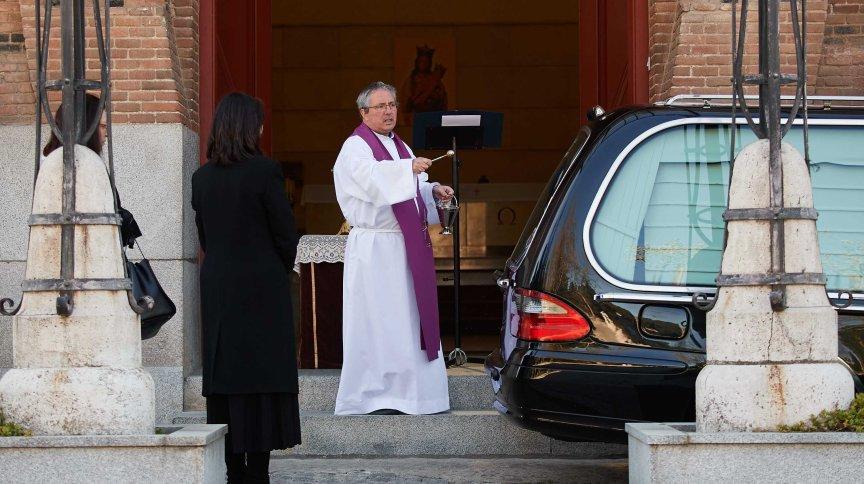 Em espécie de drive-through funerário, padre benze carro com caixão de vítima do novo coronavírus em Madri, na Espanha