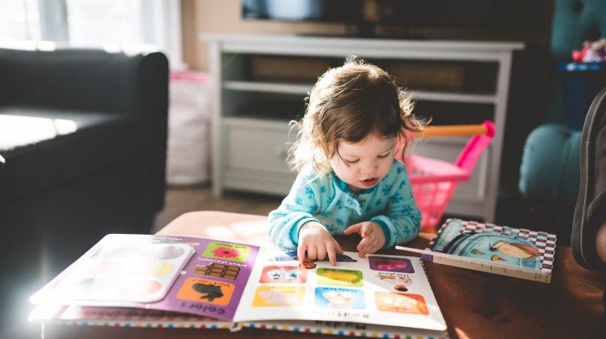 Criança lê livro em casa. Confinamento é propício para aproximar pais e filhos na leitura