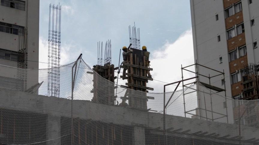 Empregados trabalham em construção de prédio residencial: duas construtoras planejam abertura de capital