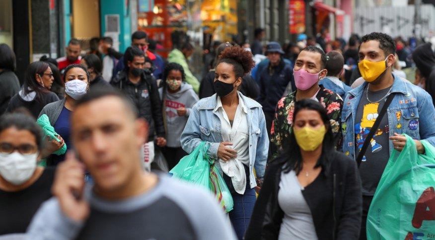 Pessoas com máscaras faciais caminham em rua de comércio popular em São Paulo durante pandemia de Covid-19
