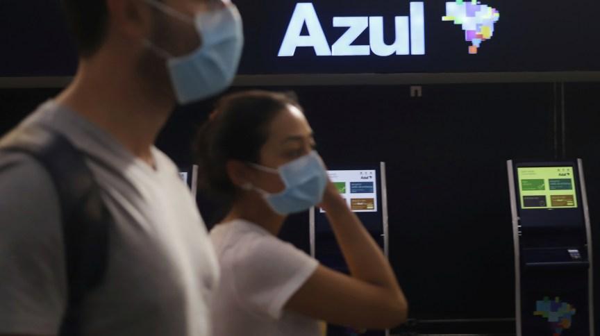 Passageiros com máscaras de proteção caminham em frente a guichês da Azul no aeroporto de Congonhas, em São Paulo (11.mar.2020)