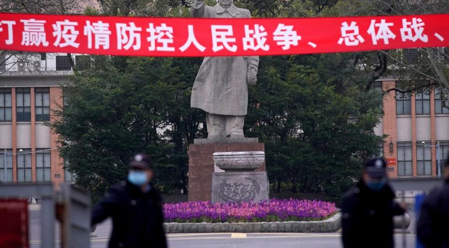 Guardas com máscara de proteção em frente a estátua de Mao Tse-Tung em Xangai