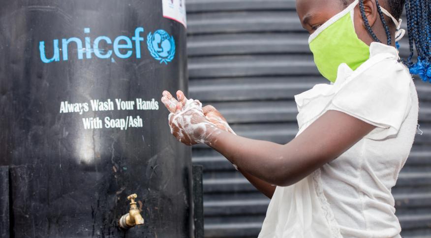 Precious, de 9 anos, lava suas mãos em estação de higienização montada pela Unicef em assentamento na cidade de Nairóbi, no Quênia