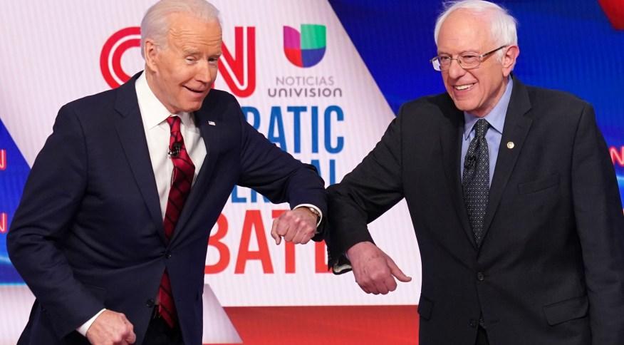 Em debate, Joe Biden (à esq.) e Bernie Sanders (à dir.) se cumprimentam usando os cotovelos por conta de pandemia de coronavírus