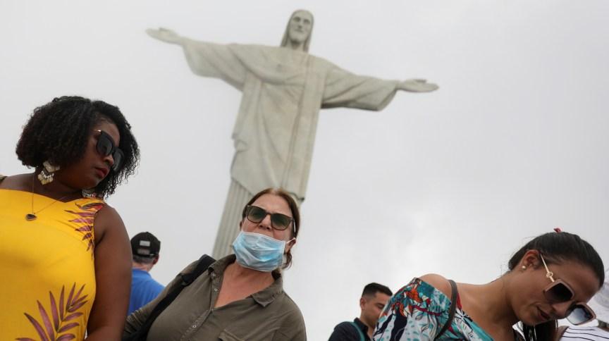 Turista usa máscara em meio a surto do novo coronavírus durante visita ao Cristo Redentor, no Rio de Janeiro
