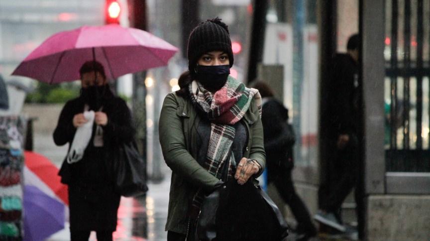 Pedestres se protegem do frio e da chuva na Avenida Paulista, região central de SP