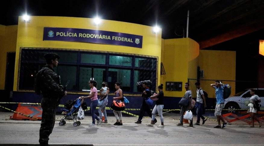 Militar brasileiro observa venezuelanos que entram no país por Pacaraima, em Roraima