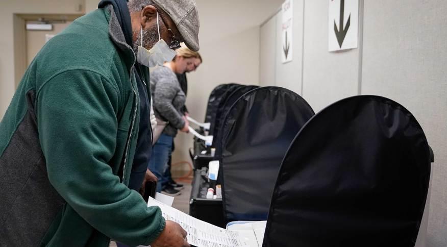 Eleitor se registra para votar nas primárias americanas de Cincinnati, Ohio, usando máscara