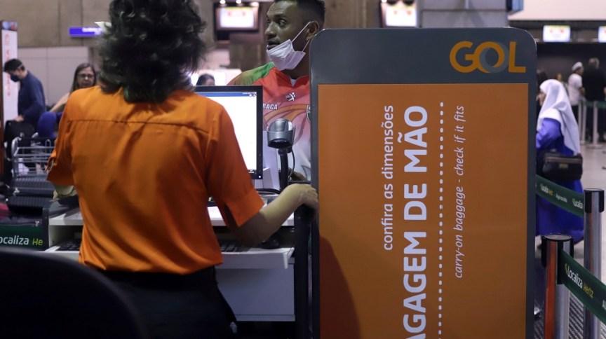 Homem usa máscara de proteção durante check in em balcão da Gol, em meio à epidemia de coronavírus (12.mar.2020)