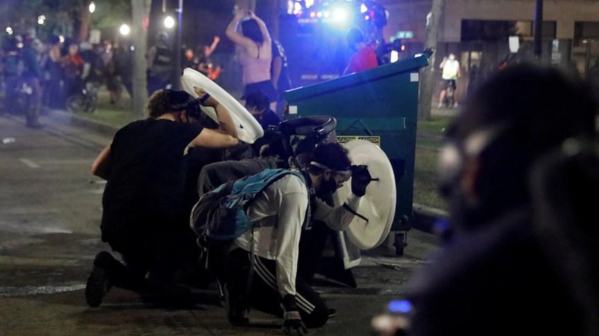 Manifestantes se protegem durante confronto com a polícia em Kenosha, no Wisconsin