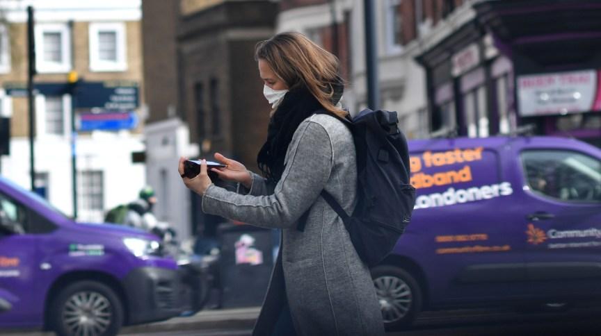 Mulher usa máscara enquanto caminha por Londres