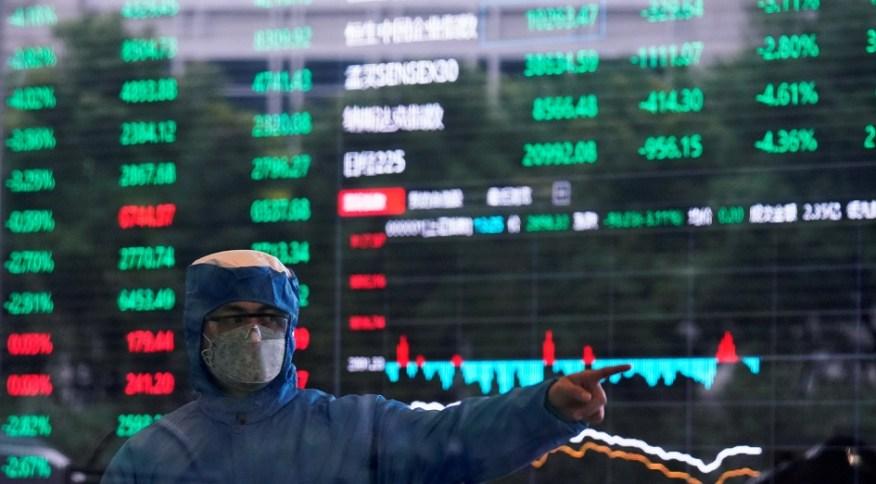 Funcionário usando roupa de proteção contra coronavírus dá orientações dentro da bolsa de valores de Xangai em 28/2/2020