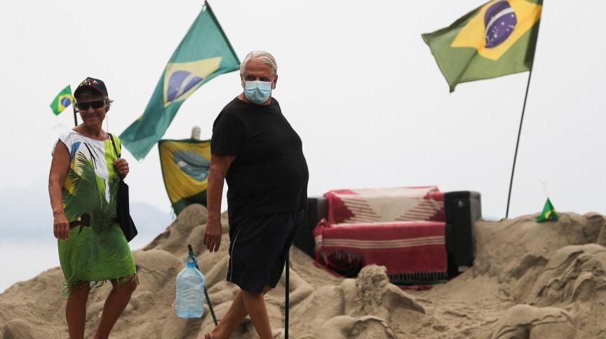 Homem usa máscara para se proteger de coronavírus na praia de Copacabana, Rio de Janeiro