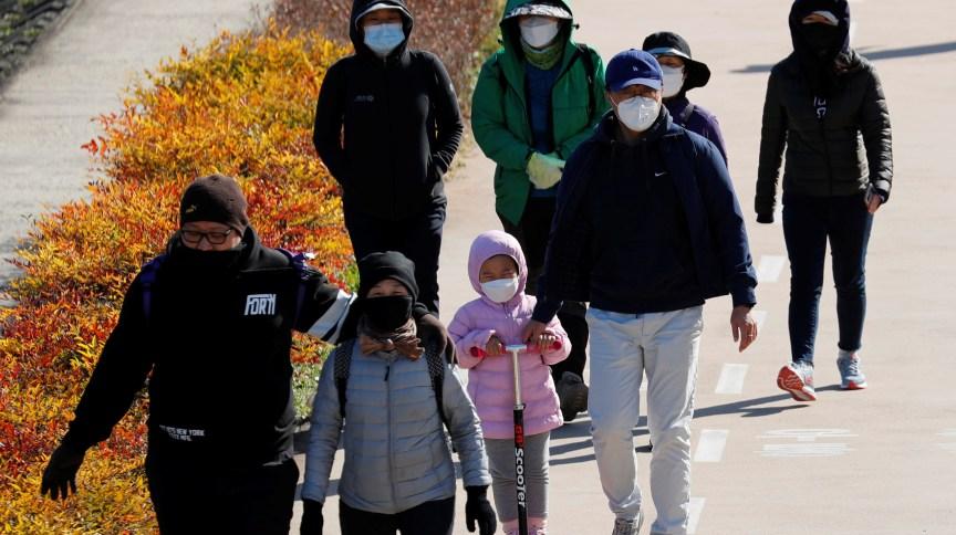 Família caminha em Daegu, na Coreia do Sul, usando máscaras em meio à pandemia do novo coronavírus