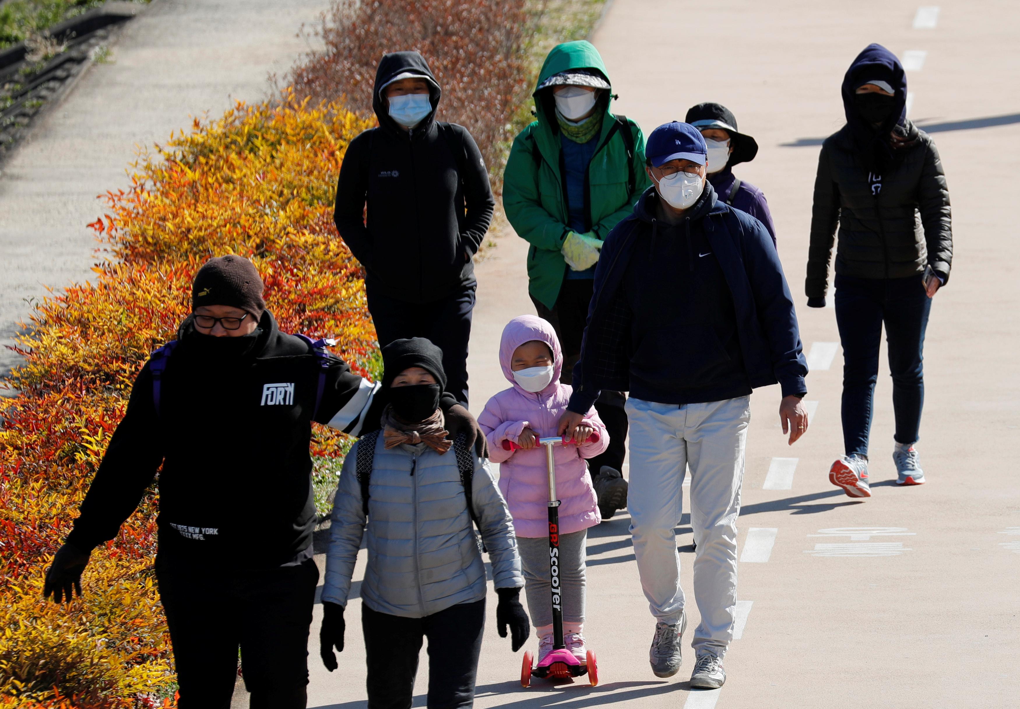 Família caminha em Daegu, na Coreia do Sul, usando máscaras