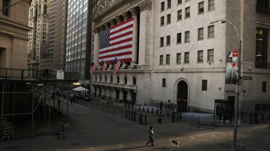 Homem caminha pela Wall Street, em Nova York, em meio ás preocupações com o avanço do coronavírus nos EUA