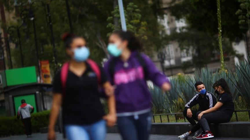 Pessoas utilizam máscara de proteção enquanto conversam em praça no México