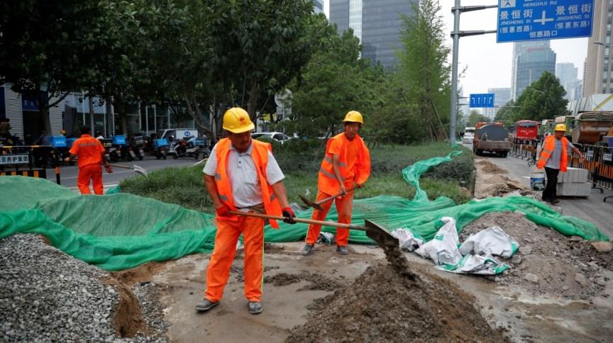 Homens trabalham em construção em Pequim