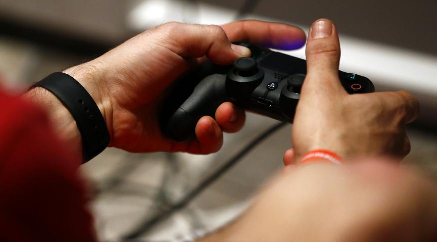 Jogador com o controle do PlayStation 4, da Sony
