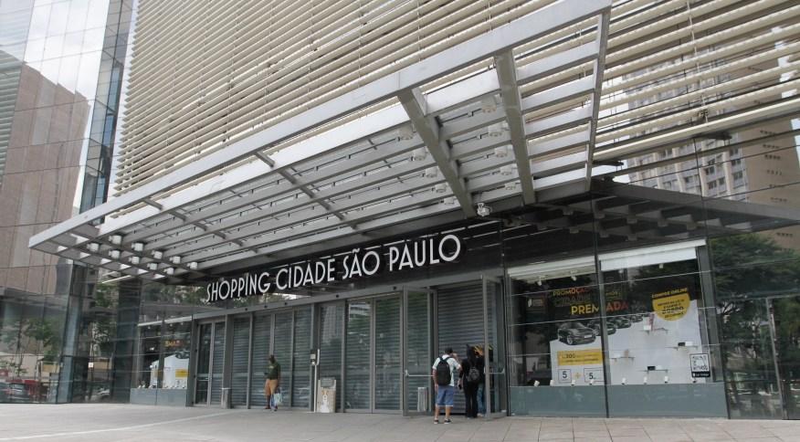Pouquíssimos pedestres passam pela fachada do Shopping Cidade São Paulo, na Avenida Paulista, região central da capital, fechado para o público, a partir desta quinta-feira (19)