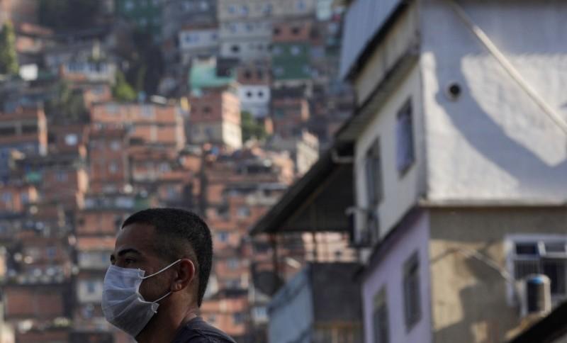 Com máscara de proteção, homem espera ônibus na favela da Rocinha, no Rio de Janeiro