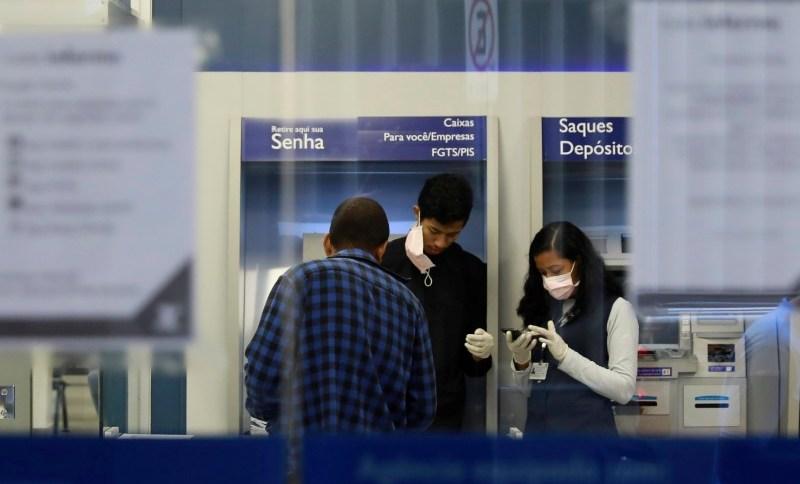 Funcionários de banco em Porto Alegre usam máscaras enquanto conversam com cliente em meio à pandemia de coronavírus