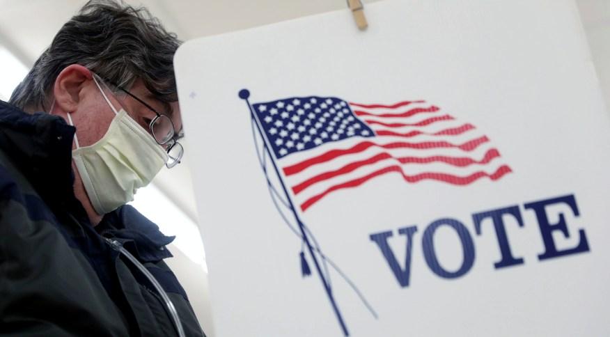 Eleitor vota nas primárias de Illinois, nos Estados Unidos, usando máscara de proteção contra coronavírus