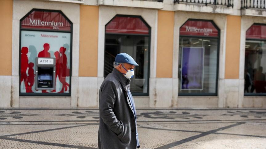 Homem de máscara caminha em Lisboa, capital de Portugal: país contabilizou 2.608 novos casos de Covid-19 na sexta-feira (16), maior número desde o início da pandemia