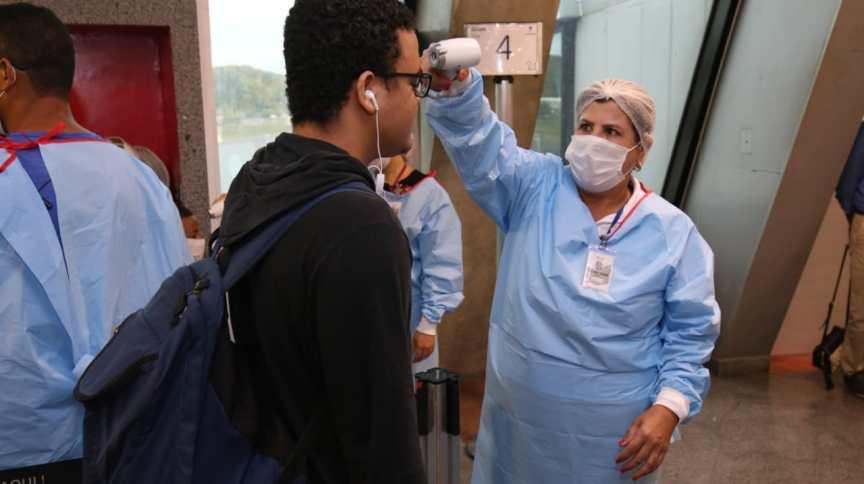 Funcionário da Secretaria da Saúde da Bahia mede temperatura de passageiros no aeroporto de Salvador