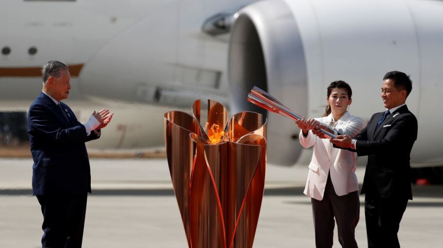 Os medalhistas de ouro olímpicos Tadahiro Nomura e Saori Yoshida posam depois de acender a chama olímpica, ao lado de Yoshiro Mori, presidente do comitê organizador das Olimpíadas de Tóquio 2020