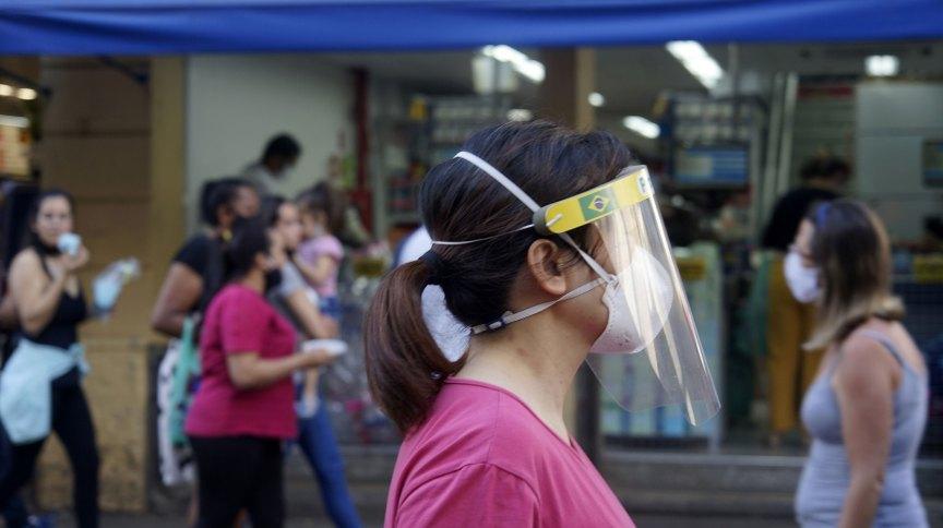 Pedestre usa máscara e face shield ao andar pela 25 de março, rua de comércio popular em São Paulo, durante pandemia da Covid-19