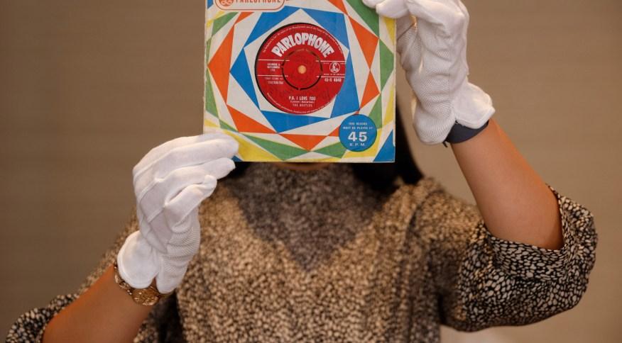 """Funcionária da Sotheby's segura primeira prensagem do single """"Love Me Do"""", dos Beatles, em Londres (25/09/2020)"""