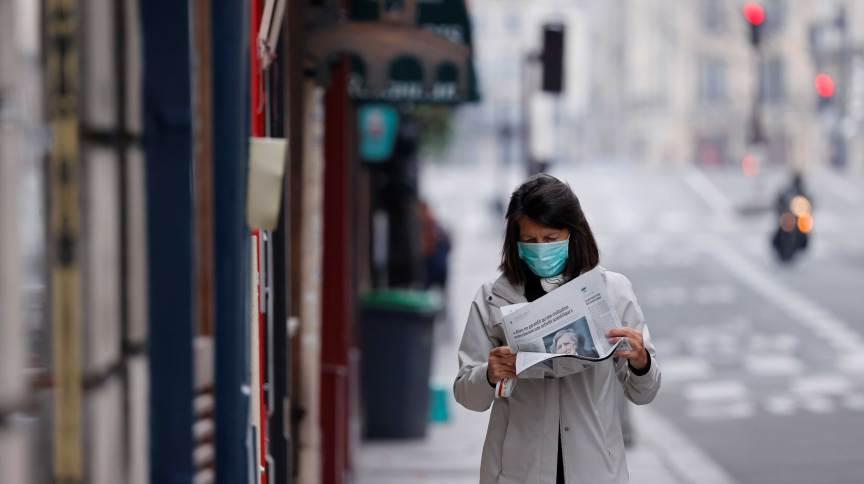 Mulher usando máscara protetora lê o jornal em rua deserta de Paris, França