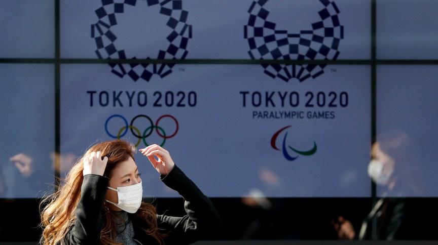 Um transeunte usando uma máscara protetora após pandemia do novo coronavírus (COVID-19) passa por uma tela exibindo logotipos dos Jogos Olímpicos e Paraolímpicos de Tóquio 2020 em Tóquio