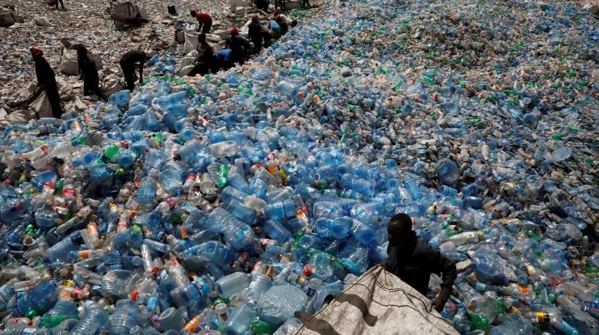 Empregados manipulam embalagens numa fábrica de reciclagem de plástic